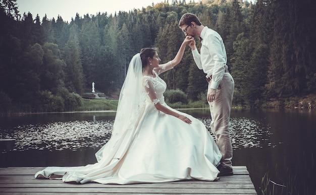 Huwelijksreis. de bruid en bruidegom knuffelen aan de oever van het meer.