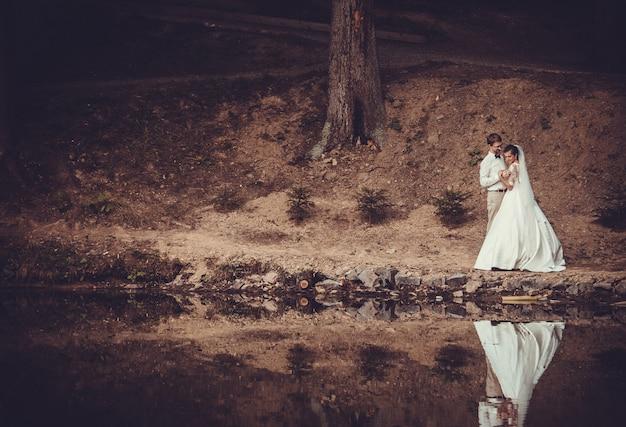Huwelijksreis. de bruid en bruidegom knuffelen aan de oever van lake.
