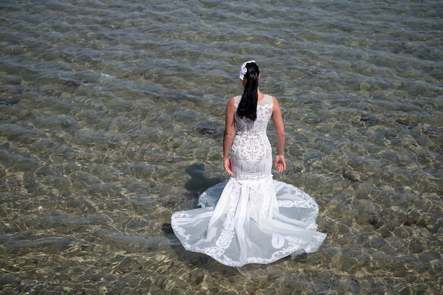 Huwelijksreis in badplaats. trouwen in het buitenland. huwelijksceremonie kust. bruid witte trouwjurk staan in zeewater. natte trouwjurk warme zonnige dag. bruid gelukkig geniet van zomervakantie oceaan achtergrond.