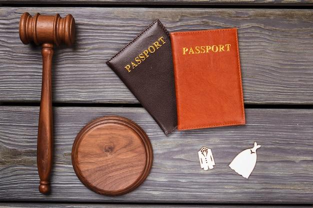 Huwelijksreis reis concept. houten hamer met twee paspoorten en bruiloftskostuums plat leggen.