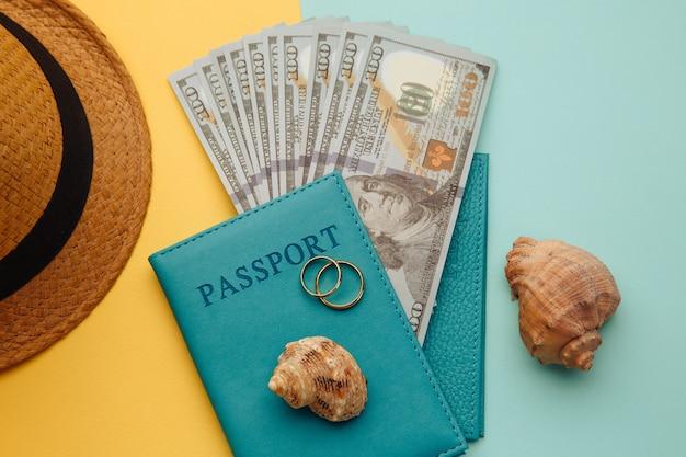 Huwelijksreis reizen concept. paspoorten met geld, toeristenhoed en schelpen op een blauwgele ondergrond