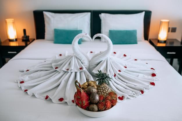 Huwelijksreis: twee prachtige zwanen gemaakt van handdoeken, gelegen op een wit bed met rozenkoekjes, met een groot bord met exotisch fruit. bruiloft.