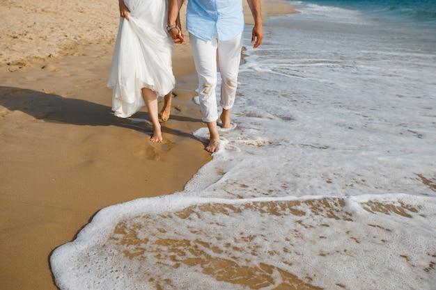 Huwelijksreis voor pasgetrouwden barefoot bruid en bruidegom in witte broek wandelen op romantisch oceaanstrand