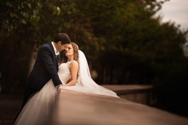 Huwelijksschot van bruid en bruidegom in park. romantisch tafereel in het park