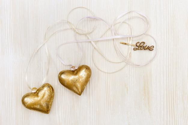 Huwelijksuitnodiging. twee harten samengebonden. witte houten achtergrond met kopie ruimte.