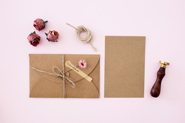 Huwelijksuitnodiging van kraftpapier op roze kleurenachtergrond