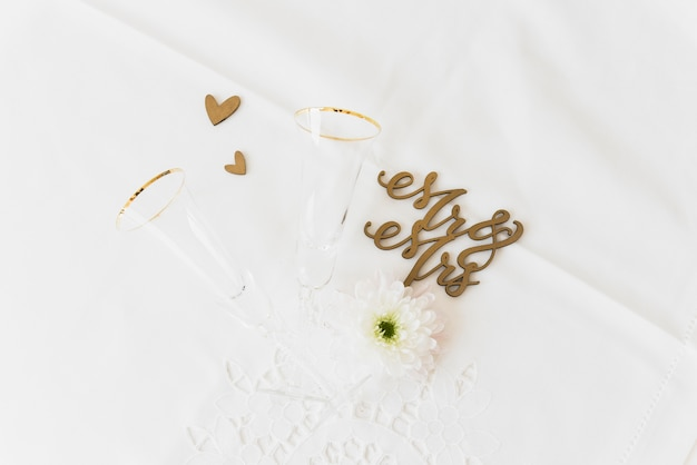Huwelijkswoord heer en mevrouw met bloem; drinkglas en hartvorm op witte achtergrond