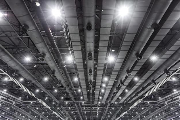 Hvac-kanaalreiniging, ventilatiepijpen in zilver isolatiemateriaal dat aan het plafond hangt in een nieuw gebouw.