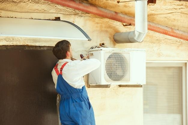 Hvac-technicus werkt aan een condensatoronderdeel voor condensatie-eenheid