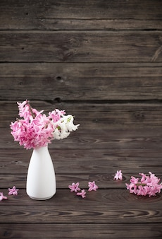 Hyacint in witte vaas op donkere oude houten achtergrond