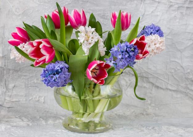 Hyacinten en tulpen in een vaas - lente achtergrond