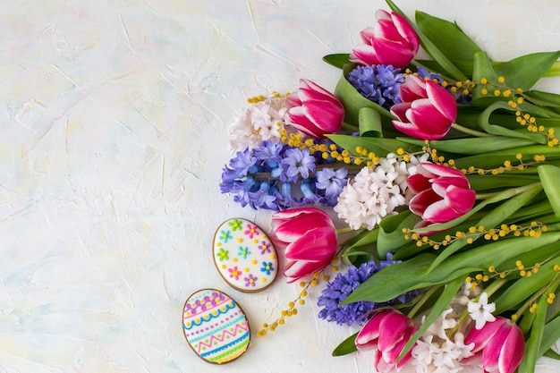 Hyacinten, tulpen, mimosa en twee paasei-vormige cakes