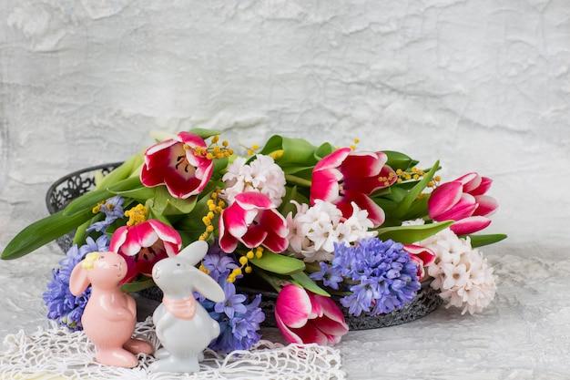 Hyacinten, tulpen, mimosa en twee porseleinen beeldjes van het konijn - pasen achtergrond