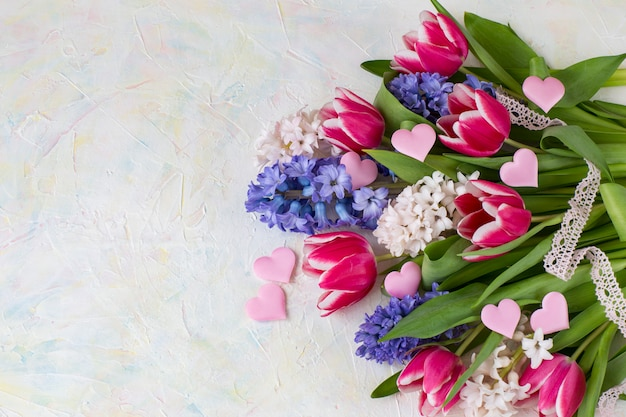 Hyacinten, tulpen, roze satijnen harten, kanten lint