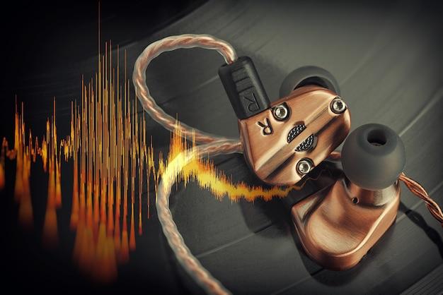 Hybride gebalanceerde armatuuroordopjes op de lp-vinylplaat met muziekgeluidsgolf