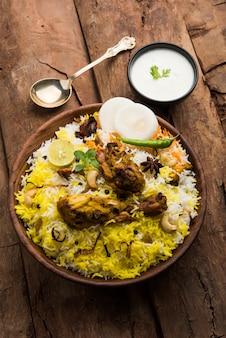 Hyderabadi kip of dum biryani, geserveerd in een kadhai of bowl met yoghurtdip. selectieve focus