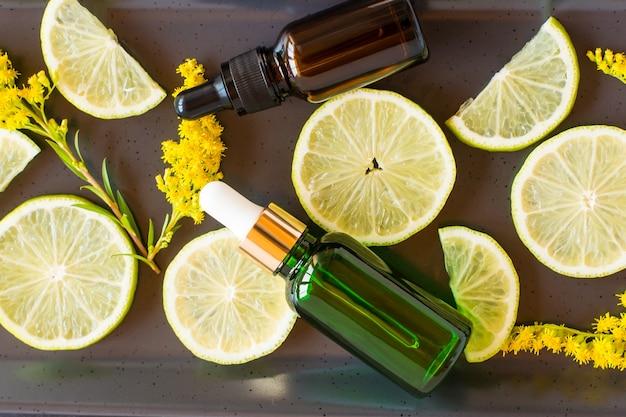 Hydraterende olie-vloeistof voor het gezicht met citrusextract in flesjes met een pipet tegen de achtergrond van schijfjes citroen en takjes solidago.