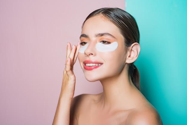 Hydraterende ooglapjes. haar huid verzorgen. vrouw die ooglapjes gebruikt die tijd thuis doorbrengen. dagelijkse verwenroutine. eerste verzorging dan make-up op. moderne cosmetica. ooglapjes concept.