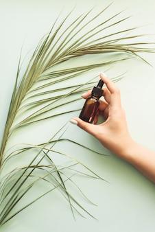 Hydraterende serum op de achtergrond van een palmblad in de hand van een meisje. blauwe pastel achtergrond. sjabloon voor reclame, blog. het concept van huidverzorging