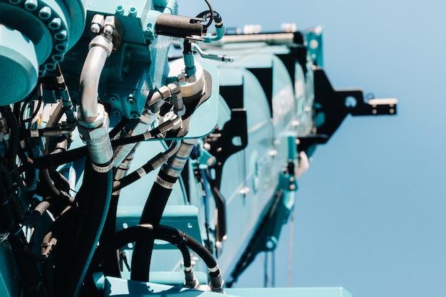 Hydraulische kraanmotor. het besturingssysteem van de kraanmotor. hydraulische afdeling hijsen op de vrachtwagenkraan. het hydraulische systeem van de motor. hydraulische slangen op de kraan. autoparts
