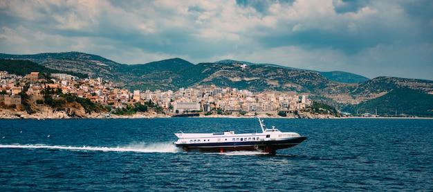 Hydrofoils boot scheert over water voor de stad kavala
