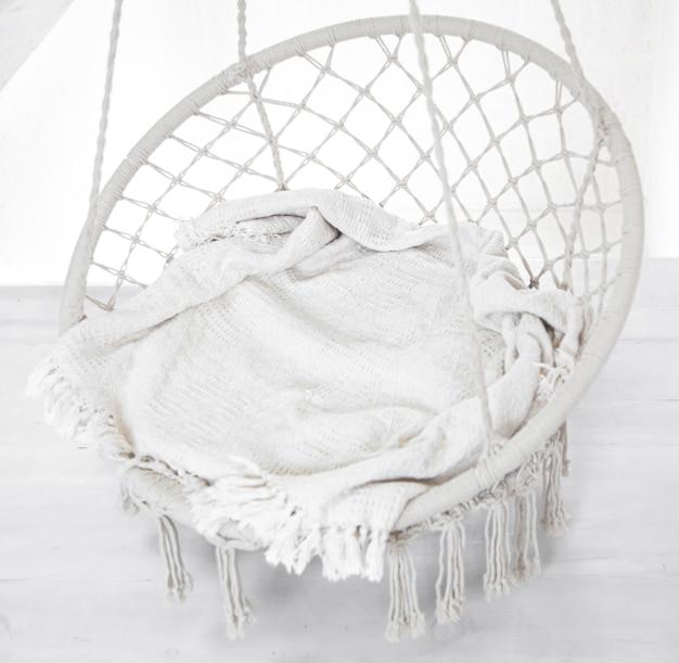 Hygge scene met witte hangstoel met grijs kussen. gezellige plek om in het weekend te ontspannen in de kamer.