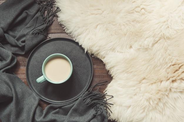 Hygge stilleven met warme kop zwarte koffie, warme sjaal op bont en houten plank.