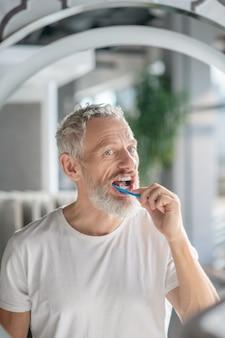 Hygiëne. een man van middelbare leeftijd die 's ochtends zijn tanden poetst