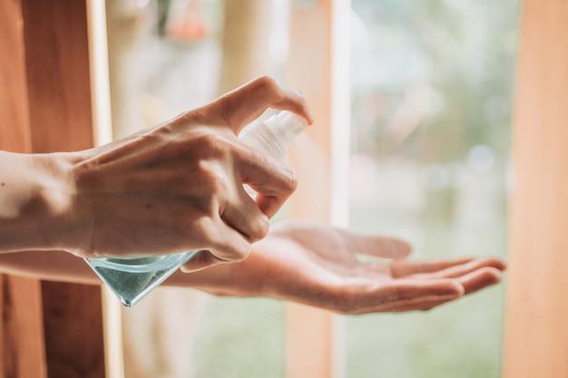 Hygiëne, gezondheidszorg en veiligheidsconcept - sluit omhoog van vrouw die antibacterieel handdesinfecterend middel sproeien