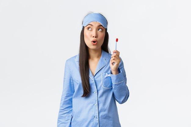 Hygiëne, levensstijl en mensen thuis concept. nadenkend aziatisch meisje in pyjama en slaapmasker heeft een geweldig idee terwijl ze haar tanden poetst, een tandenborstel vasthoudt en naar de linkerbovenhoek kijkt.