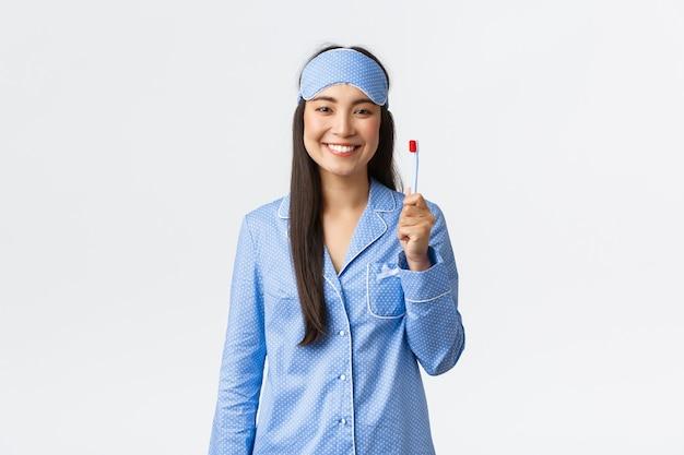 Hygiëne, levensstijl en mensen thuis concept. vrolijk lachend aziatisch meisje in pyjama en slaapmasker met tandenborstel en witte perfecte tanden, gebruik whitening tandpasta, witte achtergrond.