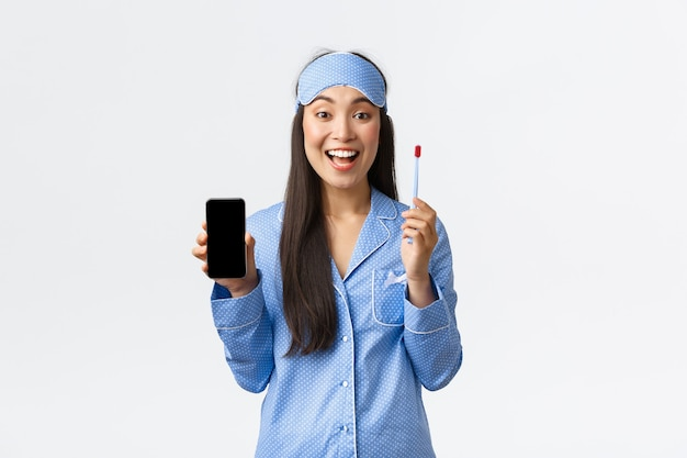 Hygiëne, technologie en mensen thuis concept. glimlachend aantrekkelijk aziatisch meisje in blauwe pyjama en slaapmasker met app om kinderen te leren hoe tandenborstels te gebruiken en tanden te poetsen, smartphone vast te houden.