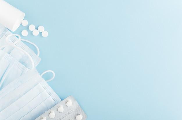 Hygiëneproducten voor mensen op achtergrond. medisch beschermend masker en verspreide tabletten