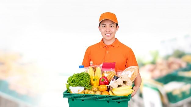 Hygiënische glimlachende aziatische man met supermarkt kruidenier dienblad doos met thuisbezorgservice