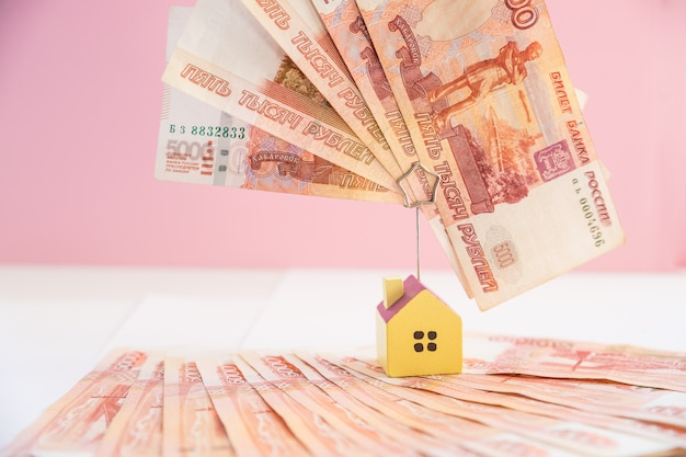 Hypotheek die onroerende goederen met het concept van de leninggeldbank laadt. geld en miniatuurhuismodel op roze achtergrond. zaken, financiën, geld besparen, bankwezen of verzekeringsconcept russisch geld.