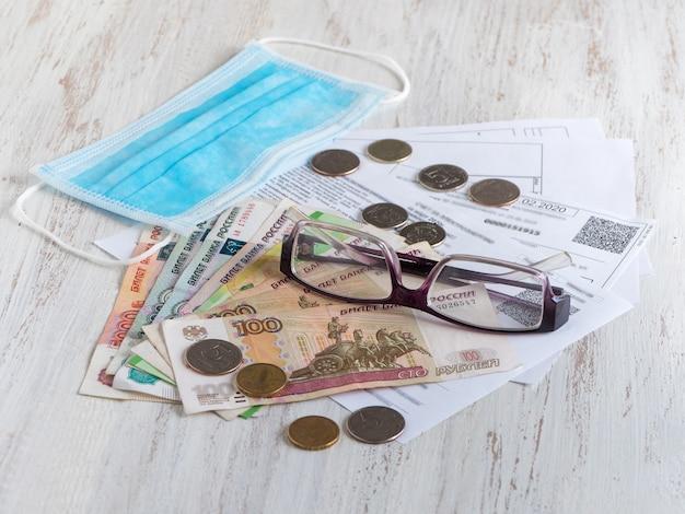 Hypotheek en nutsrekeningen, muntstukken en roebelsbankbiljetten, glazen en medisch masker op houten lijst. betaal energierekeningen in een pandemische quarantaine