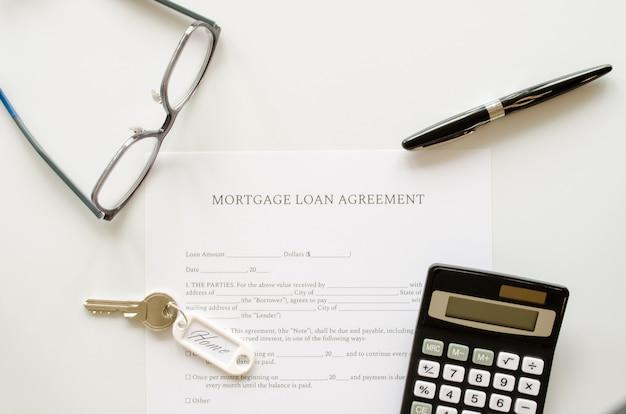 Hypotheek lening overeenkomst contract, concept met rekenmachine, sleutels en pen op hypotheek vorm of contract. bovenaanzicht.