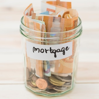 Hypotheeketiket op glaskruik met euro bankbiljetten en muntstukken