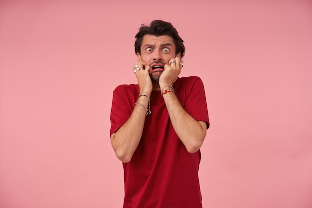 Hysrerische, gekke jongeman met stoppels in een rood t-shirt voelt zich doodsbang en ziet er in paniek uit