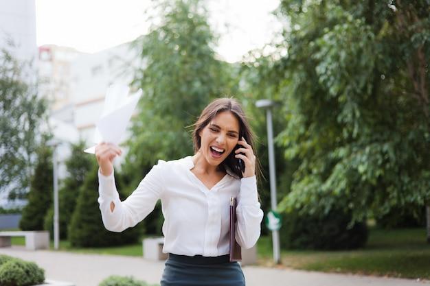 Hysterie gebracht, boze zakenvrouw gekleed in een witte blouse en een rok schreeuwt in de telefoon