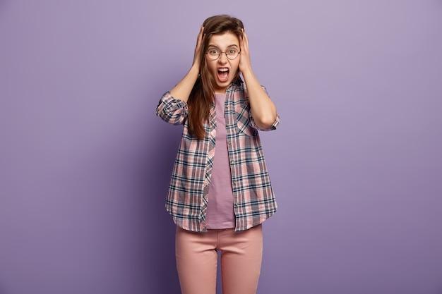 Hysterisch geïrriteerd jong vrouwtje bedekt oren met hanfds, wil niet horen klagen, boos gillen, draagt een ronde bril