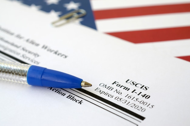 I-140 immigrantenaanvraag voor buitenaardse werknemers blanco formulier ligt op de vlag van de verenigde staten met blauwe pen van het department of homeland security