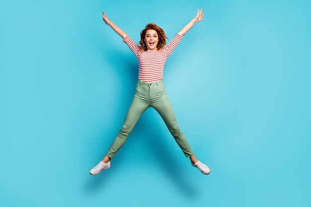 I ben beschikbaar! full body foto van gekke dame springen hoog verheugend weekend zonnige dag gespreide handen dragen casual rood wit overhemd groene broek schoenen geïsoleerde blauwe kleur
