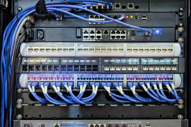 I / o-poort aan achterkant van serverrack en blauwe kabel aangesloten op lan-poort voor werk aan netwerkcommunicatie op data center