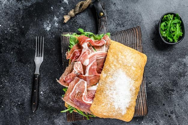 Iberico ham sandwich op ciabattabrood. zwarte achtergrond. bovenaanzicht.