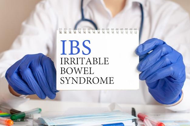Ibs-kaart in handen van arts. de arts dient blauwe handschoenen in met een vel papier met tekst ibs - afkorting voor prikkelbare darm syndroom, medisch concept.