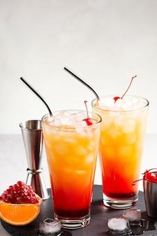 Ice tequila sunrise-cocktails op een grijze betonnen tafel naast een jigger en cocktailkers
