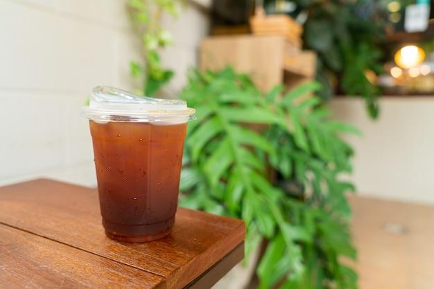 Iced americano koffie in afhaalmaaltijden glas op houten tafel