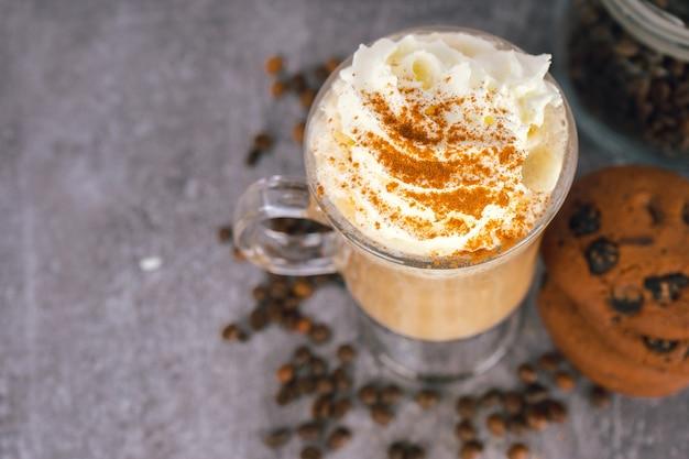 Iced caramel latte koffie in een hoog glas met slagroom op een grijze achtergrond met verstrooiing van koffiebonen. bovenaanzicht, plat leggen met kopie ruimte.