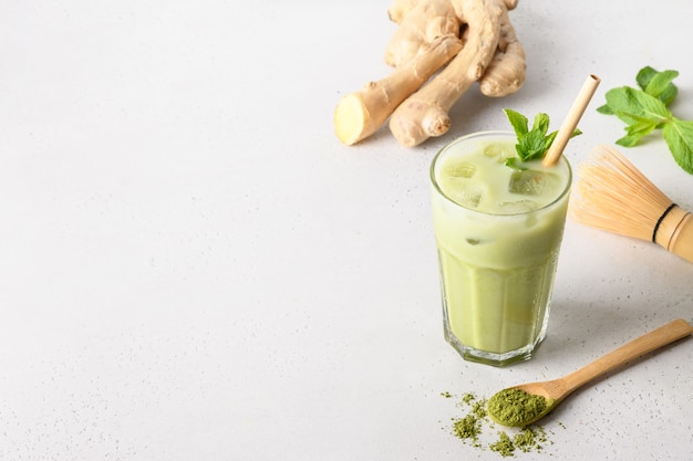 Iced green matcha thee met gember op witte tafel. close-up. verticale oriëntatie.